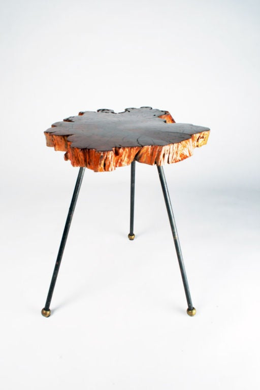 A rustic occasional side table comprised of a thick, free edge slab of cypress with deep crevasses and lacquered surface supported by three wrought iron legs each with brass ball feet, American, circa 1950.