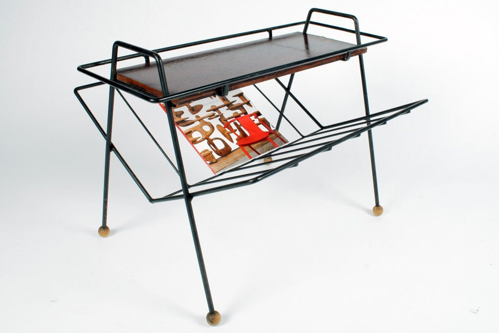 """A multifuntional magazine stand in a wrought iron frame with wooden ball feet that holds a removable tray with wrought iron handles and a wooden top. This rack was manufactured by Woodlin-Hall and was part of the """"Tempo Group"""". The item number is"""