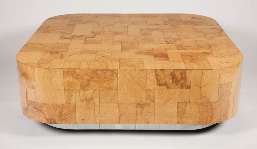 A large cocktail table from the cityscape collection with a patchwork pattern of veneers in burl wood to the top and polished chrome and brushed steel to the base. Signed Paul Evans to the base. By Paul Evans. American, circa 1970.  Please call