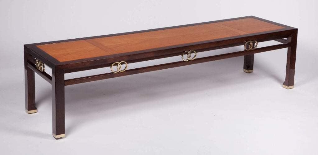An elegant rectangular cocktail table, from the Far East collection by Baker, made in dark stained walnut with an inlay of veneers in natural stained wood to the top. The table has accents to the apron of interlocking rings, as well as brass sabots