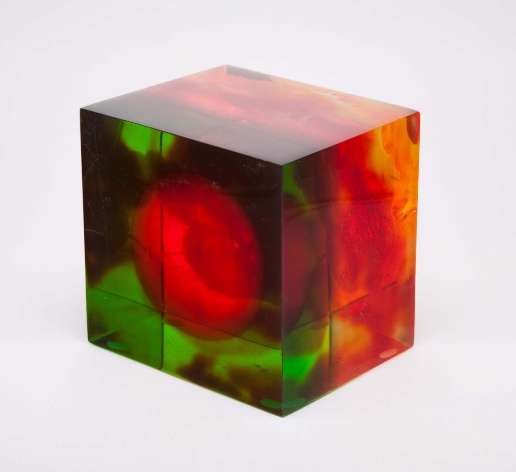 A fantastic acrylic block with layers of color: red, orange, yellow, green; each layer permeates through the next to create a three dimensional amorphic shape on one end and a perfect circle to the other. By Dennis Byng, American, circa 1970.
