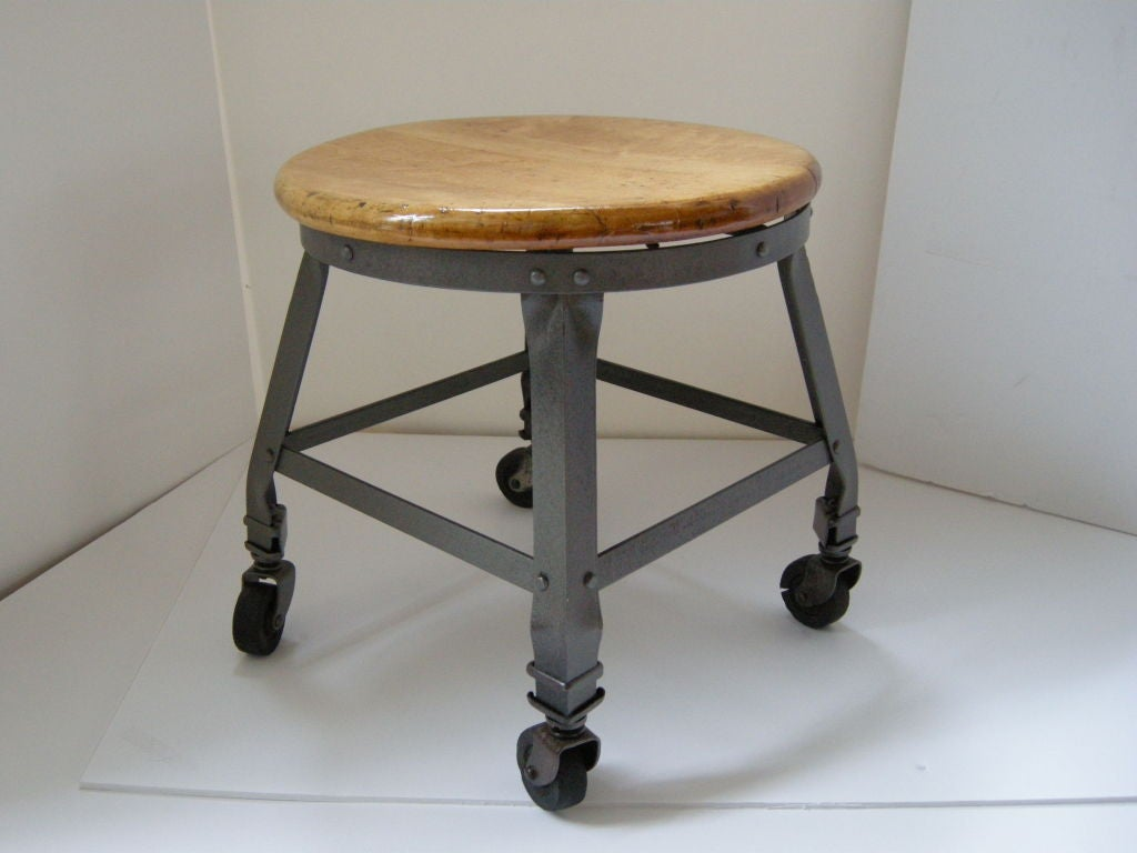 Industrial Iron Stool, on original casters. Maple Wood seat restored, polished iron.