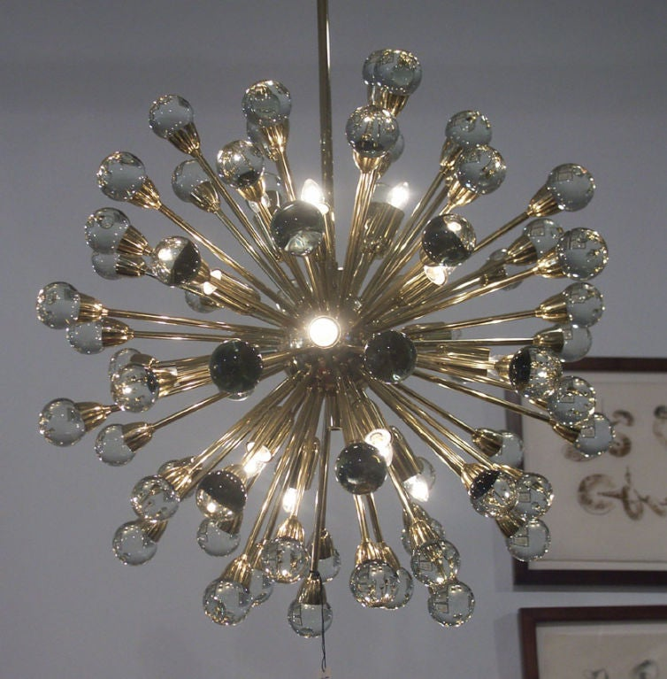 Incredible new old stock sputnik chandelier, Italy 1970's. Dozens of highly polished brass stems each with a glass orb, radiate around the central sphere.