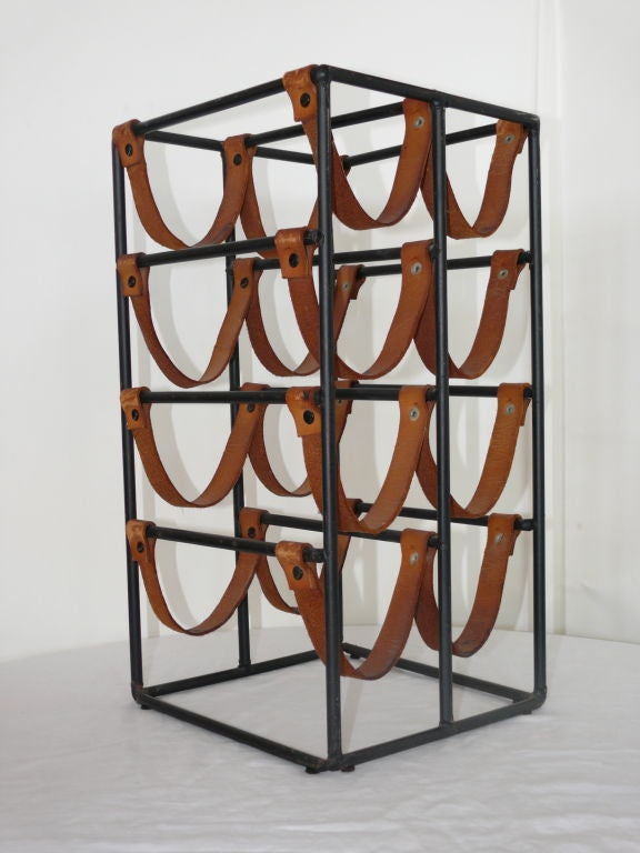 Classic Paul McCobb wine rack in black iron and original leather. Leather straps have patina with black rivets. Small and functional - and holds 8 wine bottles!