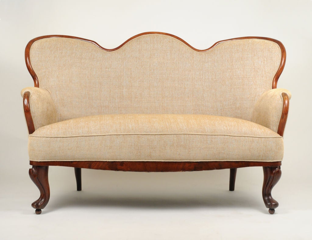 A 19th century bentwood settee with sensually curved fruitwood frame recently upholstered in Travers fabric with Samuel & Sons trim.
