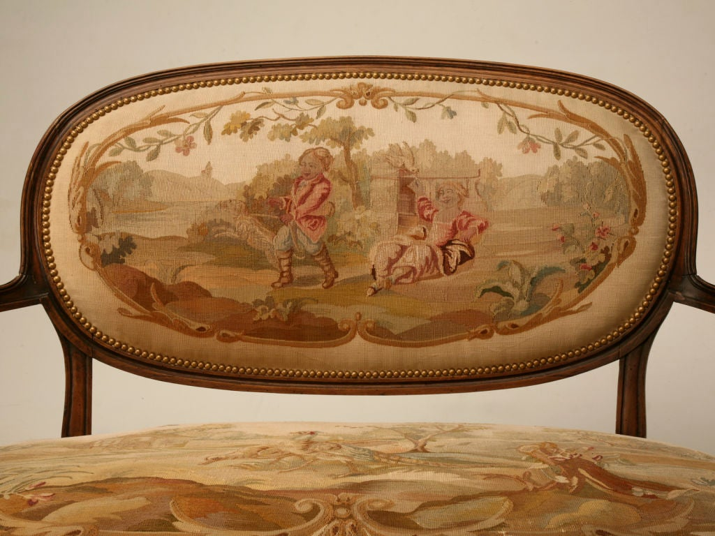 A petite (rare size) French Louis XVI fruitwood canape´ upholstered with it's original Aubusson tapestry. This fully restored settee features a desirable oval backrest with a channeled frame and nailhead trim, too. The upholstery, a pastoral scene