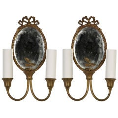 A pair of antique mirrorbacked, bow-topped sconces