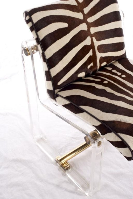 Fabulous lucite chair with brass accents.  Reupholstered in chocolate and cream stenciled cowhide.