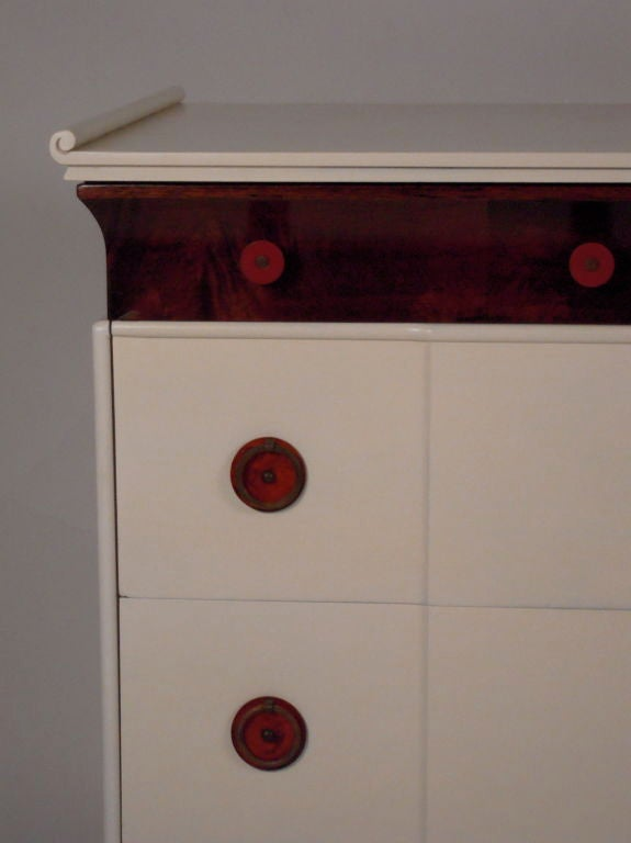 A glamorous cream lacquered and mahogany veneered chest of drawers, with chinoiserie delicately scrolled top over a richly figured mahogany veneered top frieze drawer with 4 brick red bakelite pulls, over 3 shaped lacquered drawers each with 2 with