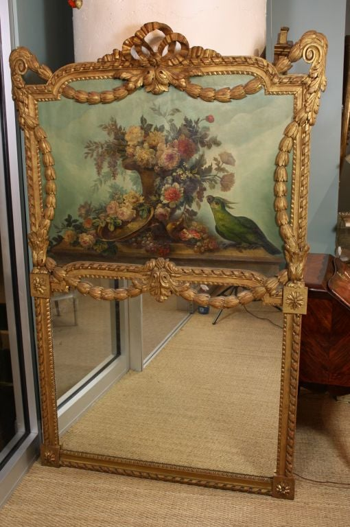 French carved giltwood mirror with beautifully detailed still life painting of flowers and urn with a green parrot. The mirror also features nicely hand-carved neoclassical elements, including ribbons, acanthus, swags and garlands. Back of trumeau