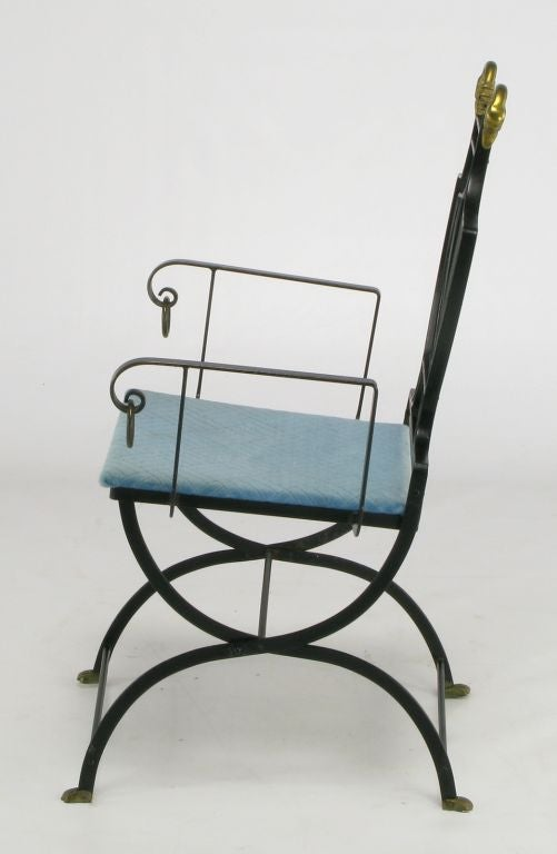 Black wrought iron arm chair with brass swan heads and brass feet. The back is the classic lyre shape and the arms feature iron rings. The seat is upholstered in a geometric patterned turquoise velvet.