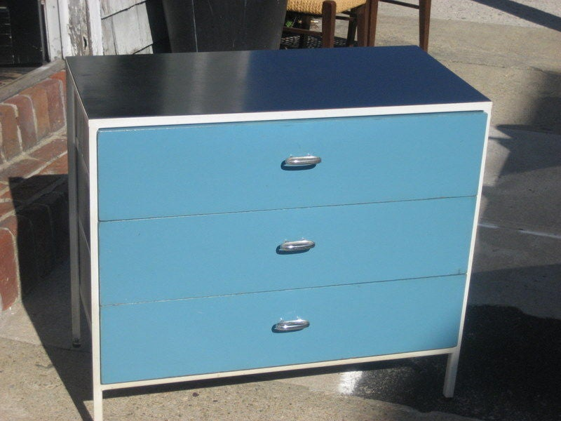A three drawer chest from the Steel Frame series by George Nelson for Herman Miller with white enameled metal frames, white laminate tops, yellow lacquered drawer faces and elliptical chrome pulls. American, circa 1950.