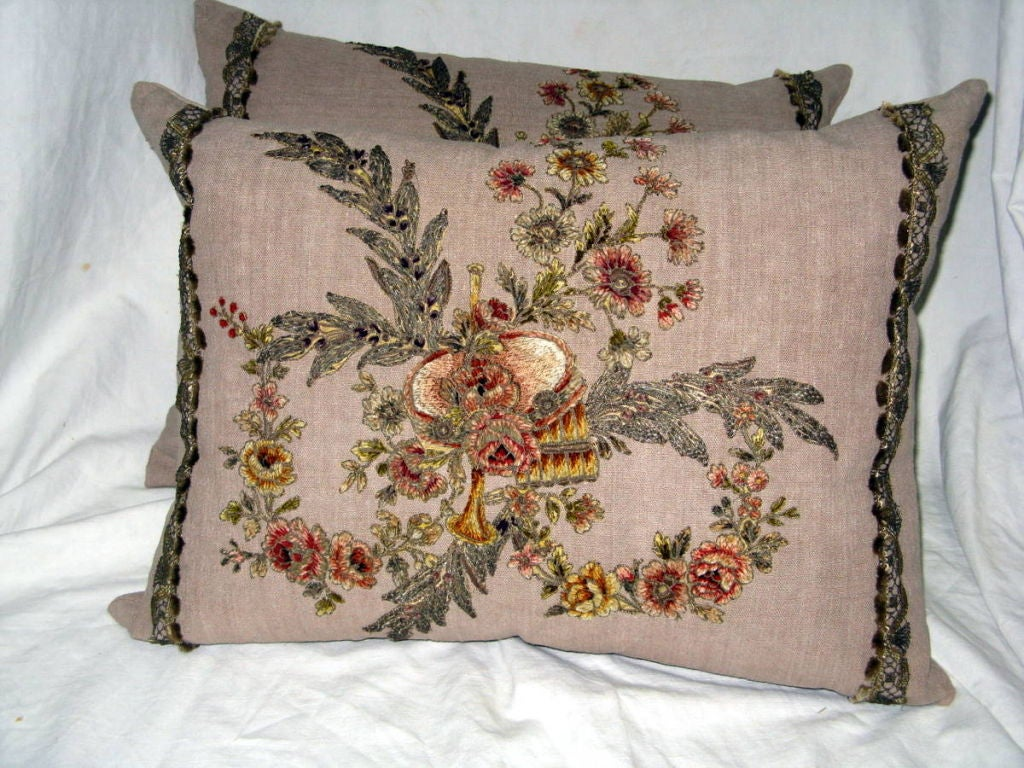 Pair of 19th century metallic & chenille embroidered appliqued linen pillows. The pillows depict musical instruments surrounded by garlands of flowers and metallic laurel leaves. There is a metallic tape trim at both sides of the pillow as a