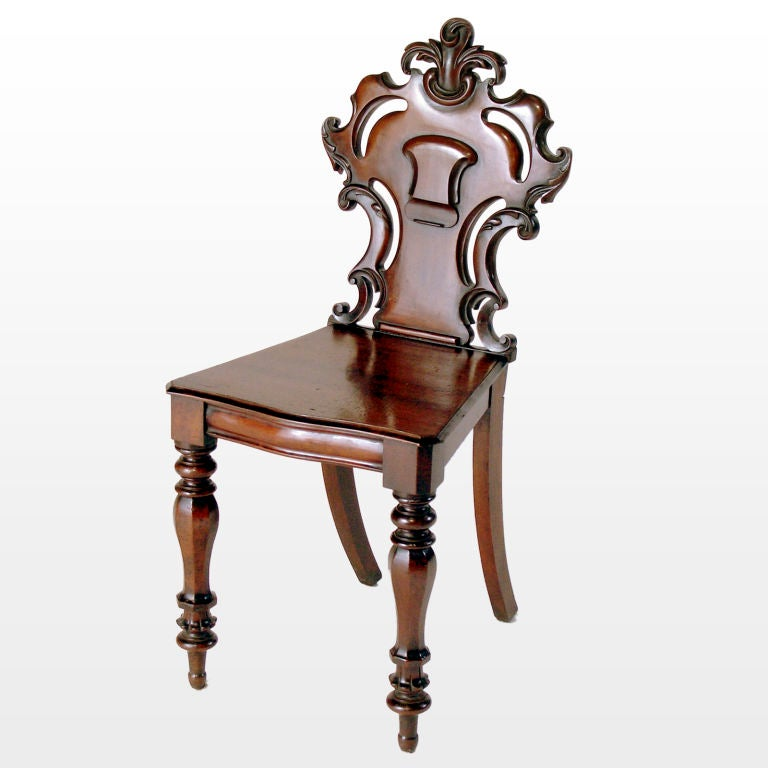 Pair of richly patinated English mahogany hall chairs with carved scrolled backs supporting fleur-des-lis crowns and raised centerpiece medallions on turned legs. Sold as a pair only.