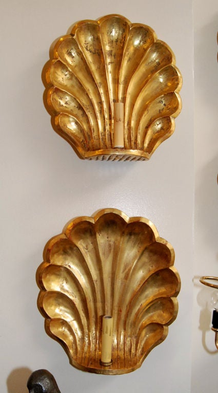 Pair of hand-carved wood shell design wall sconces with 22-karat gold finish.