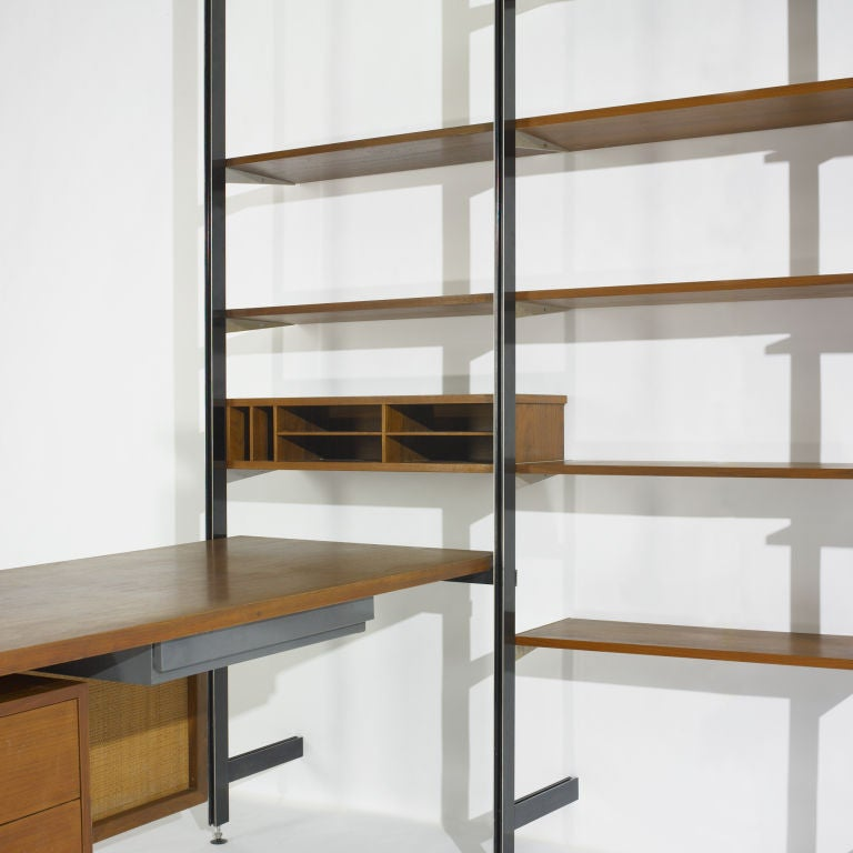 This storage unit is comprised of a three part desk, privacy screen, four uprights, seven shallow shelves, four deep shelves, one document cabinet and one waste basket. Signed with decal label to upright: [CSS Comprehensive Storage System] and disc