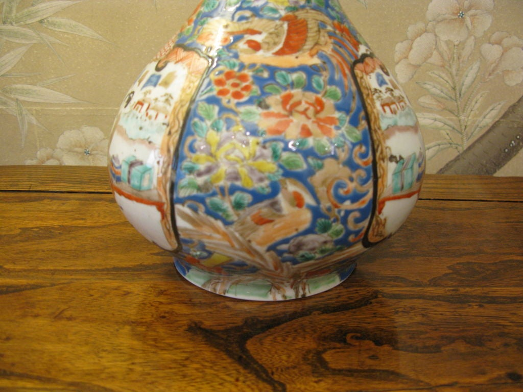An interesting and boldly colored antique Japanese Kutani vase, probably dating to the Taisho Period (1912-1926). -With design of landscape and figures within panels, and ornate floral and bird designs between panels. -Signed on base.