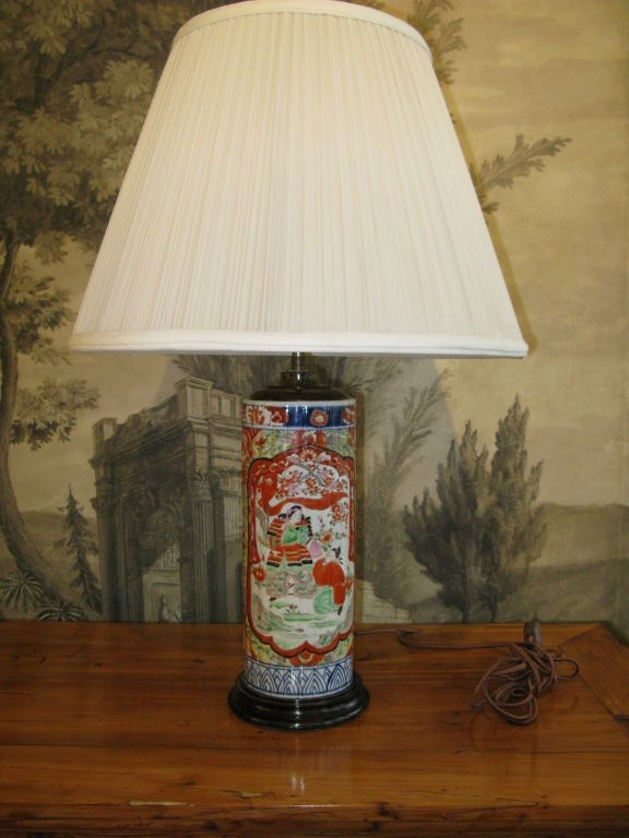 A ribbed cylindrical antique Japanese Imari vase, drilled and mounted as a lamp. Bold design in blue, orange, yellow, green and black. Geometric and floral borders, with reserves of figural design.