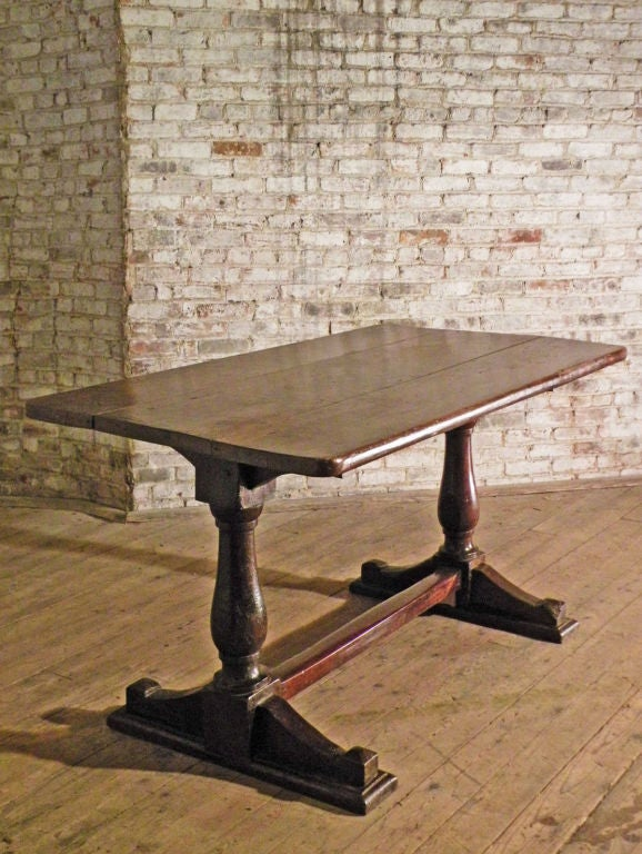 Beautiful, well proportioned trestle table with a rich patina. The three-plank top supported by baluster-turned legs on each end, ending in shoe feet, connected by a square stretcher.