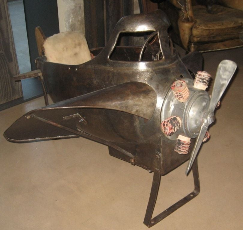 Vintage metal carnival plane from the 1920's. Plane came from a vintage carnival ride. The plane has a movable propellor and upholstered seat.
