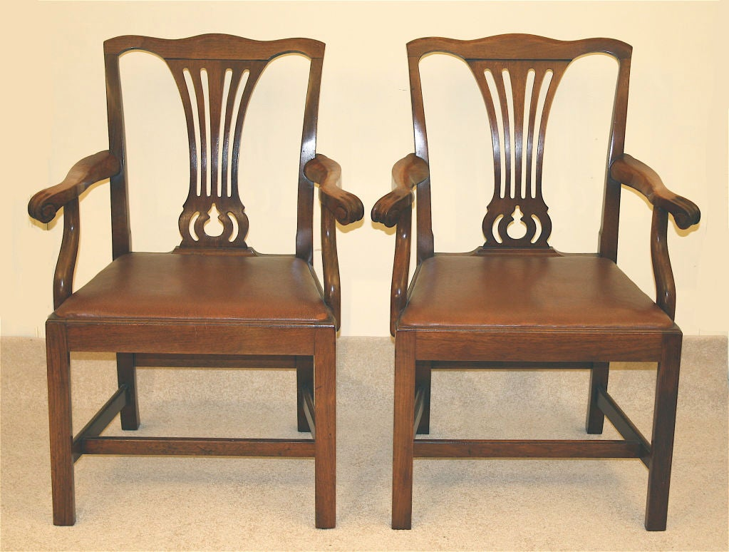 An American Centennial pair of leather seated knuckle armchairs of dense, heavy, honey colored mahogany; with pierced vasiform splats, marlborough legs, and four stretchers. Originally for a partners desk; suitable as library or hall chairs, or even