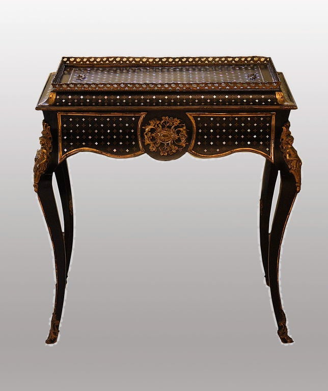 An ebonised Louis XV influenced, ormolu mounted, mother of pearl and ormolu inlaid jardiniere with shelf; that converts to a galleried small center or side table, when its top is in place to cover the tin removable planting container.  Attributed to