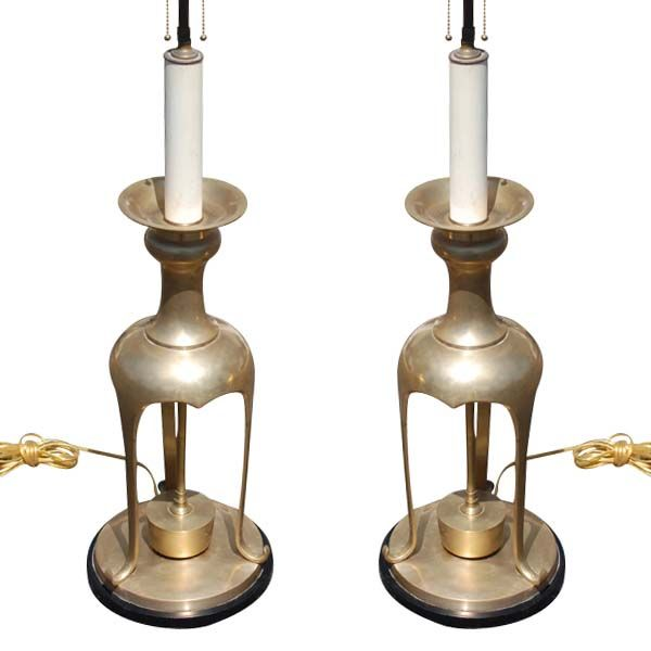 A pair of large brass table lamps in the manner of James Mont. Tripod form with round black bases.