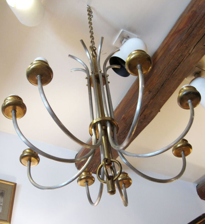 Sober and gracefully shaped 8-arm chandelier in brass and silvered metal. The branches are tied together by 2 rings decorated at the top with small ball. A double ring sets the chandelier at the bottom.