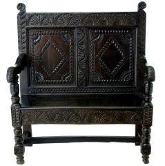 A 17th Century style carved oak panel back oak settle