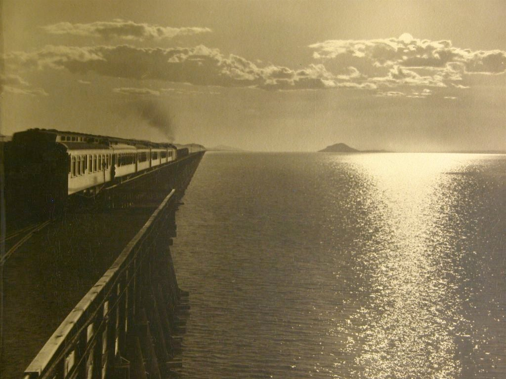An early artistic photograph of a locomotive and the setting sun in a surreal vista over water.