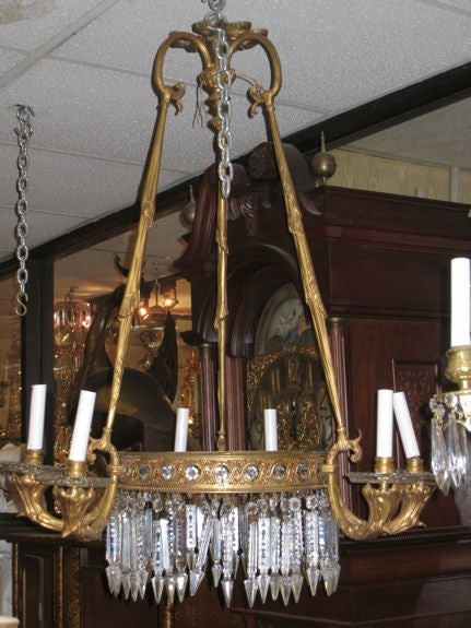 This lovely chandelier in the French Empire style features a central ring with reticulated guilloche motif, hanging crystal pendants, six candle arms and three upright supports with draper motif.