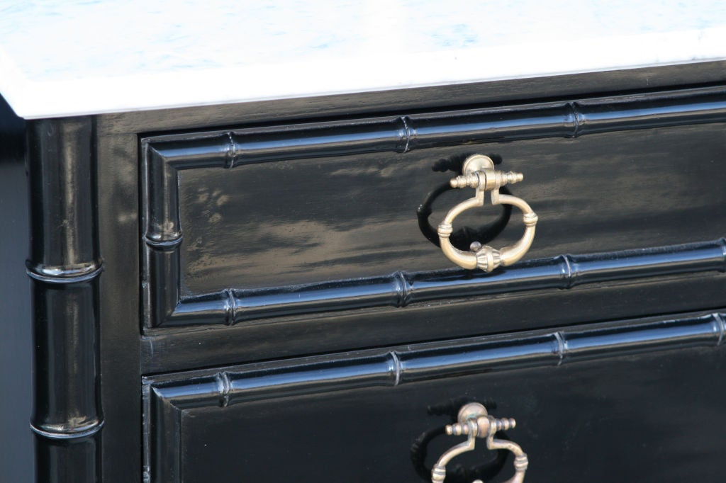 Stunning high polished black lacquer over hand hewn mahogany faux bamboo dresser with highly detailed cast bronze drop pulls finished with a white marble top with ogee edge detail.