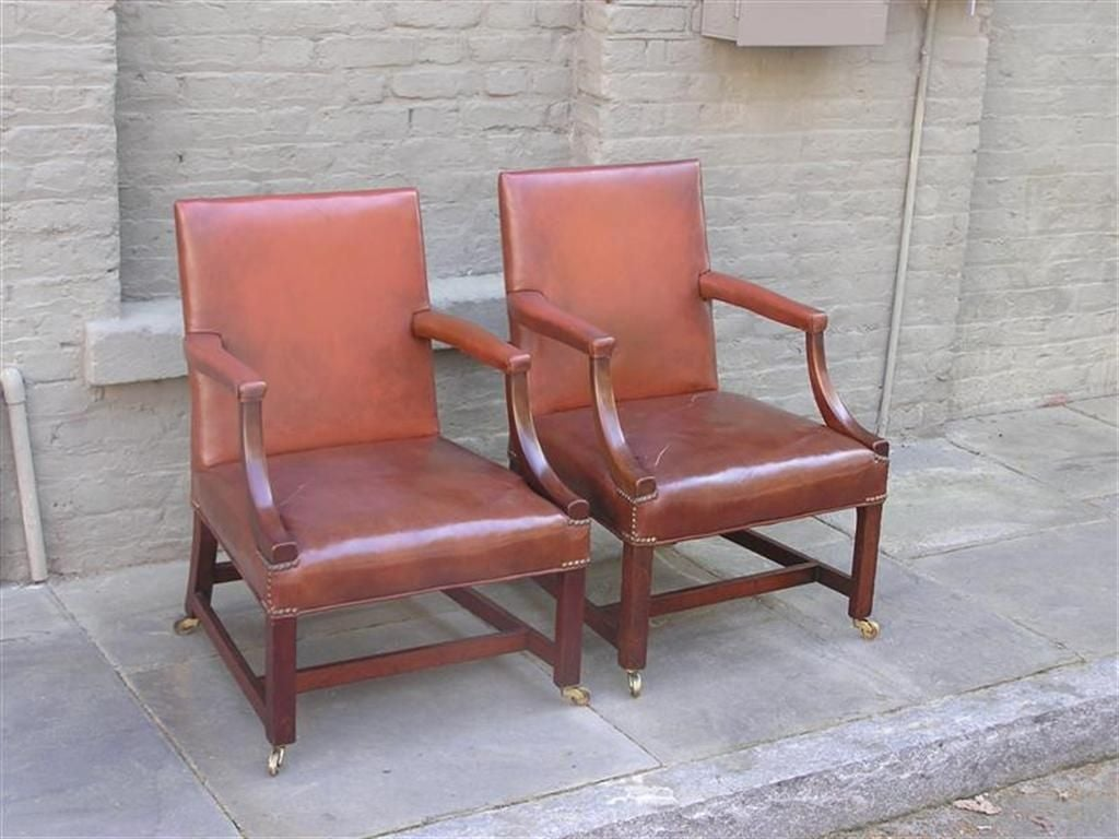 Pair of English Chippendale mahogany gainsborough leather arm chairs with original brass casters.