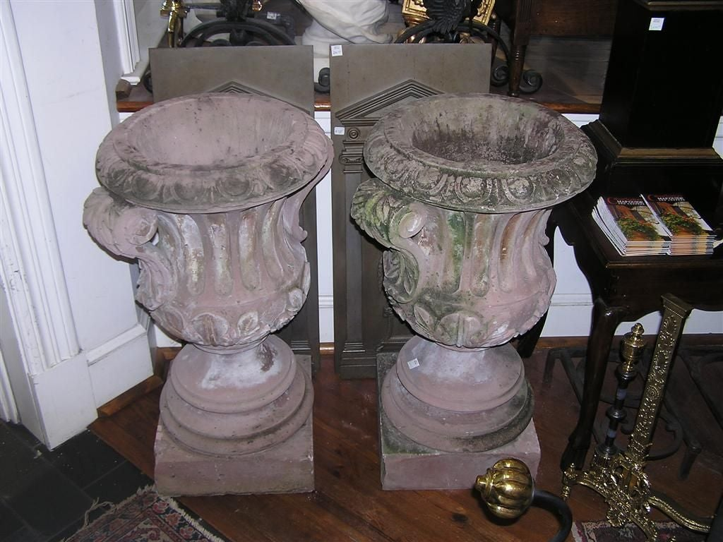 Pair of Italian hand carved sandstone campaign urns with carved egg & dart borders, acanthus scrolled side handles with fluted centers, each terminating on circular squared plinths.  Late 18th Century.