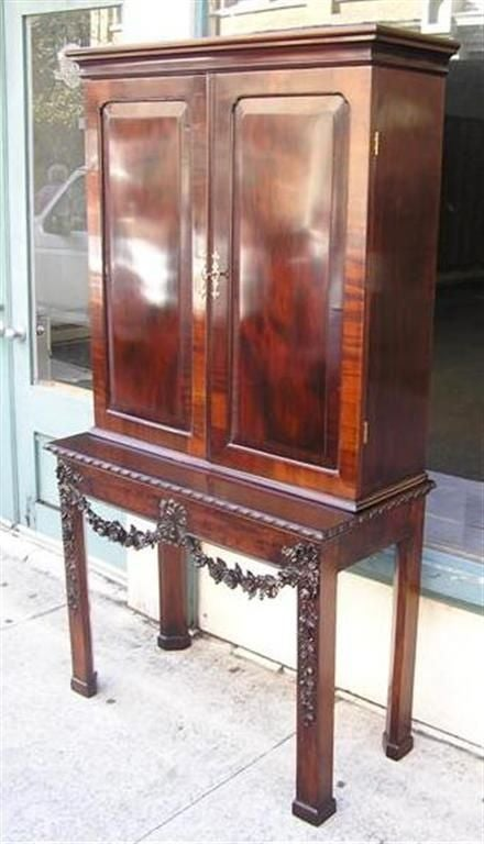 English Chippendale mahogany desk / bookcase on stand with flanking book matched doors, gadrooned molded edge, fitted interior pigeon holes over four drawers, adjustable interior shelving, hand caved ribbon & floral garland motif, and terminating on