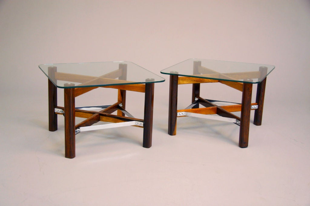 A unique pair of Brazilian rosewood side tables with chrome supports and glass tops. See matching coffee table as well. Beautifully refinished with a hand-rubbed French polish. 