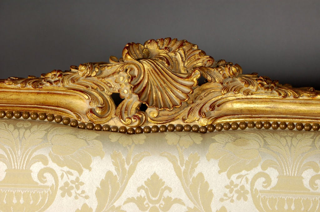 Beautiful satin damask upholstered, ornately carved Louis XV Settee, with nailhead trim.