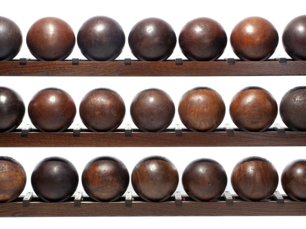 A three-row oak bowling ball rack comprised of twenty-seven (27) regulation sized antique lignum vitae; (heartwood) lathe turned bowling balls.