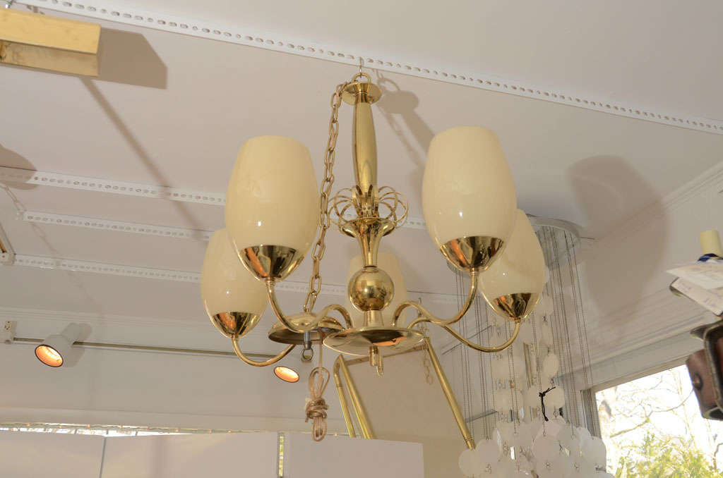 Five-arm brass chandelier with opaque glass globes.