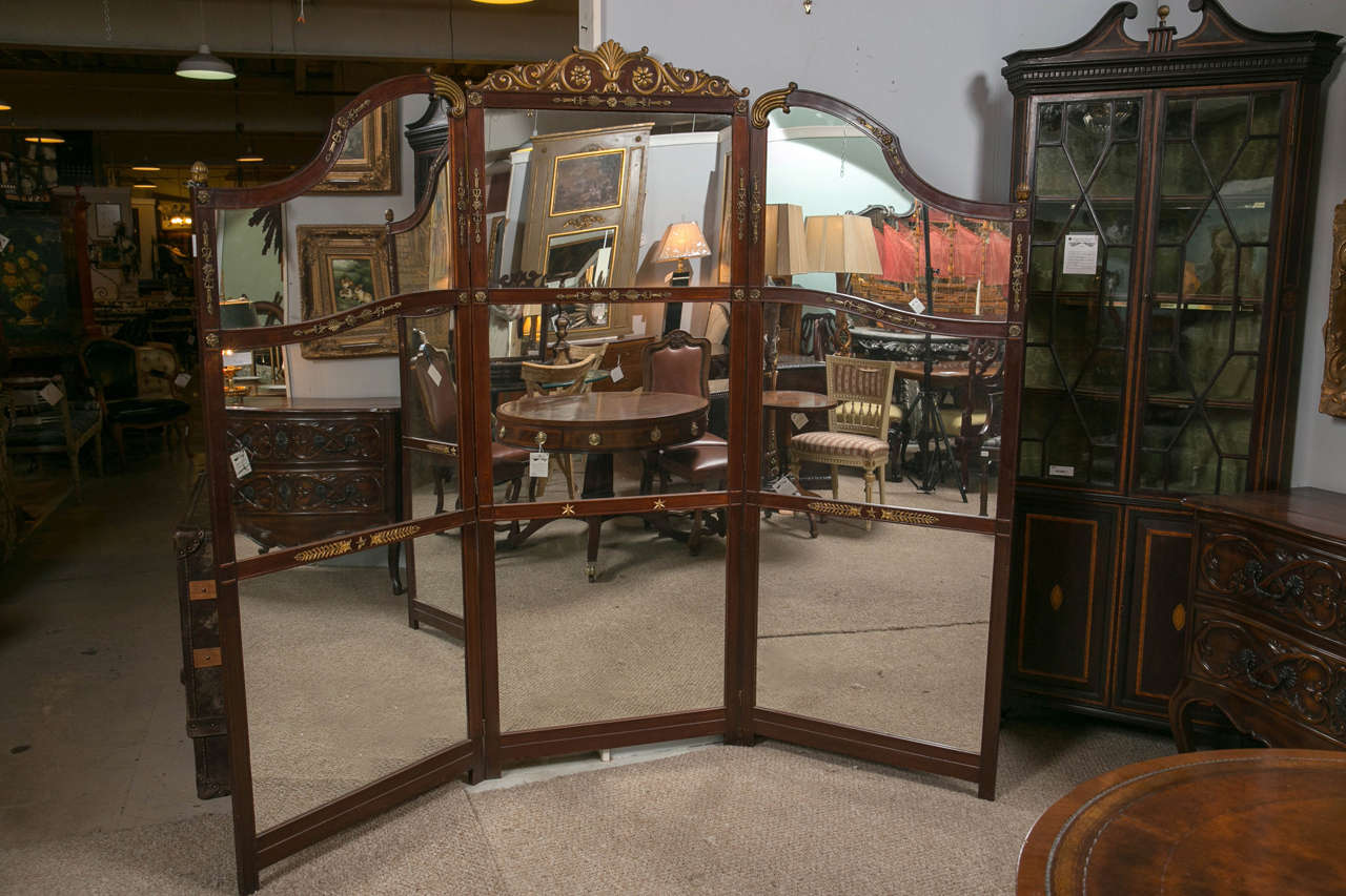 This wonderful and large room divider or screen has nine mirror panels framed in a fine mahogany grained wood decorated with bronze mounts. This highly functional screen is extremely decorative and would fit in any room with most all interiors. This