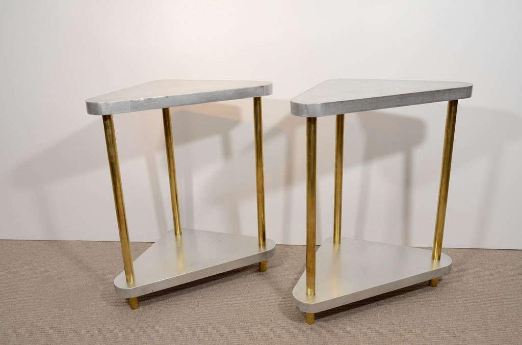 Triangular satin steel tables with three tubular brass uprights.
