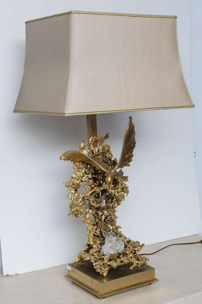 Sculptural lamp in golden bronze by Boeltz  representing a Flying  eagle  ornamented by rock Crystal included in gilted metal structure golden bronze and rock crystal makes the piece like a piece of jewelry. The light of the lamp, gives to the