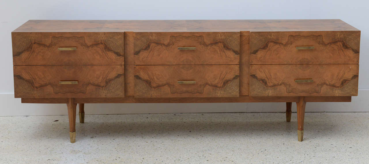 All-over in exotic root wood veneers, comprising six drawers over tapering legs terminating in brass caps.
