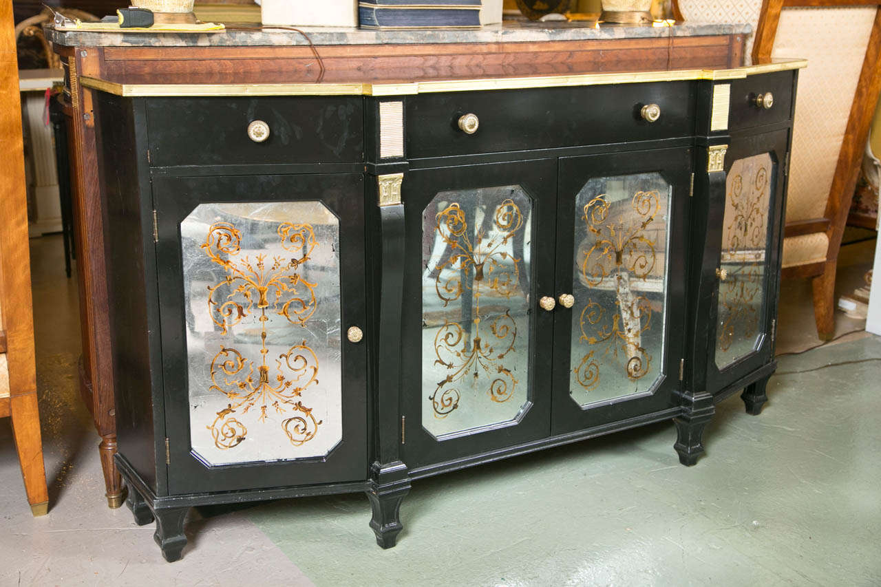 Hollywood Regency style ebonized sideboard, the bronze banded top over a frieze fitted with three drawers, atop a conforming cabinet decorated with verre églomisé glass doors, raised on short squared legs, by Jansen.