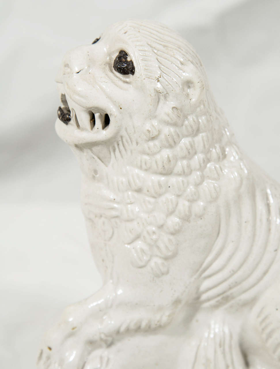 Salt glazed pottery figure of a lion made in England in the mid-18th Century. The body is covered in a beautiful smoky gray colored salt glaze. The figure was slip-cast and has sharp definition in the molded mane, and ribs. The notable eyes and