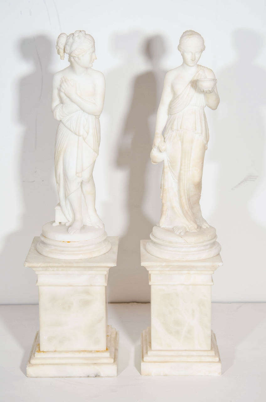 A pair of fine antique neoclassical hand-carved alabaster figures of Grecian ladies on carved alabaster bases.