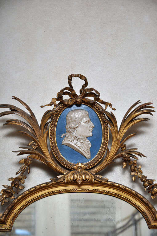 French Louis XVI style carved gilded wood mirror, ornamented with floral, swags and garlands, surmounted by oval blue and white male portrait.