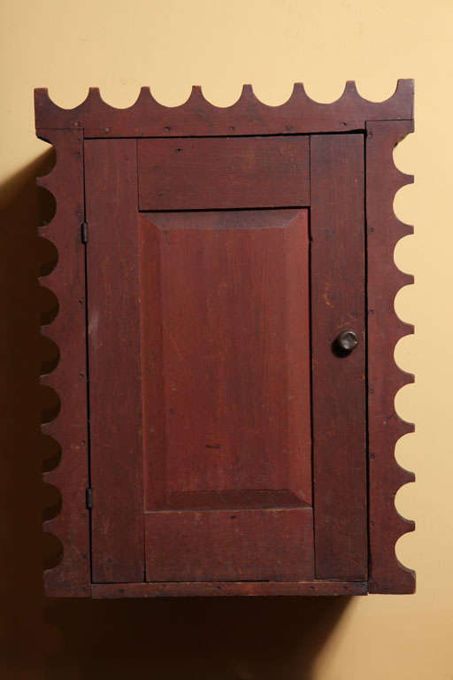 Rare and exceptional hanging wood wall cupboard in original red paint.  Raised panel door.  Unique scalloped border.  Three shelves inside.  American.  New England or New York State origin.  Circa 1830.