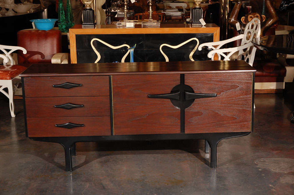 A Modernist credenza / small buffet in American walnut with two tone finish. Has three drawers and a cabinet.