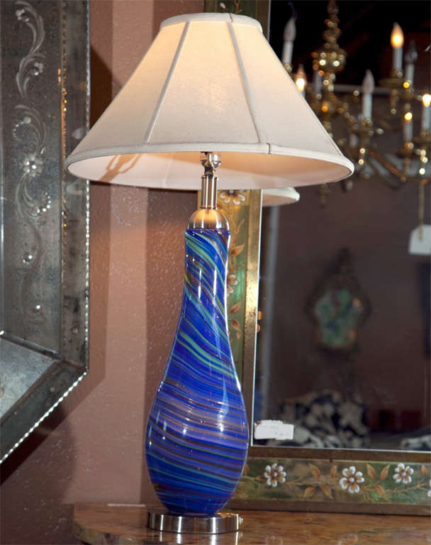 Pair of vintage Murano glass style table lamps. Each multi color one-piece glass lamps sitting on a chrome base with a matching chrome lidded top. The pair light in the interior as well as the top light bulb or both. The swirling painted center